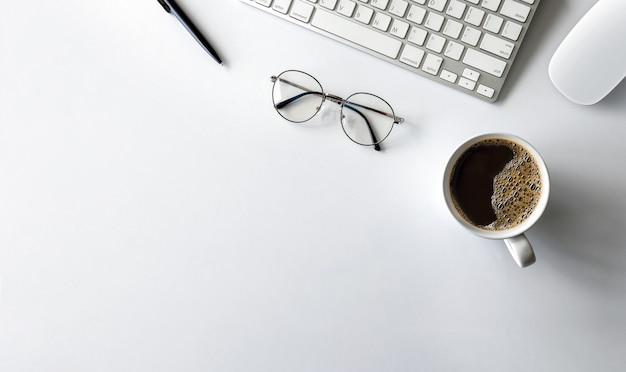 Vista superior del espacio de trabajo del escritorio de oficina con taza de café, teclado y horario de trabajo en la mesa blanca