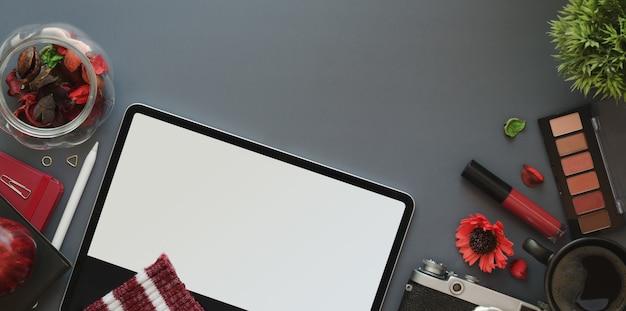 Vista superior del espacio de trabajo femenino de lujo rojo con tableta sobre fondo de escritorio gris oscuro con maquillaje y útiles de oficina