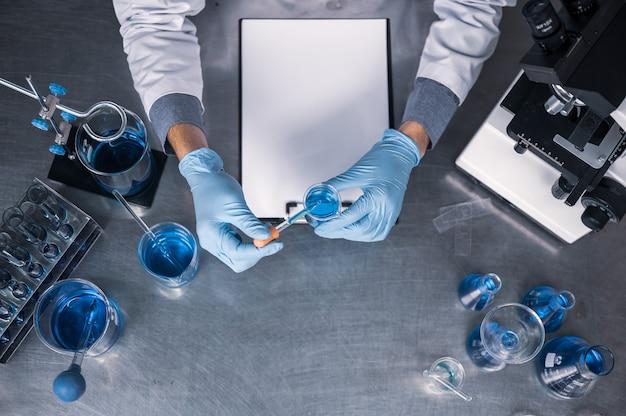 Vista superior del espacio de trabajo en laboratorio con microscopio, computadora portátil y herramientas de laboratorio
