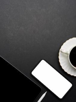 Vista superior del espacio de trabajo laico plano creativo oscuro con teléfono inteligente, tableta, taza de café y espacio de copia, trazado de recorte