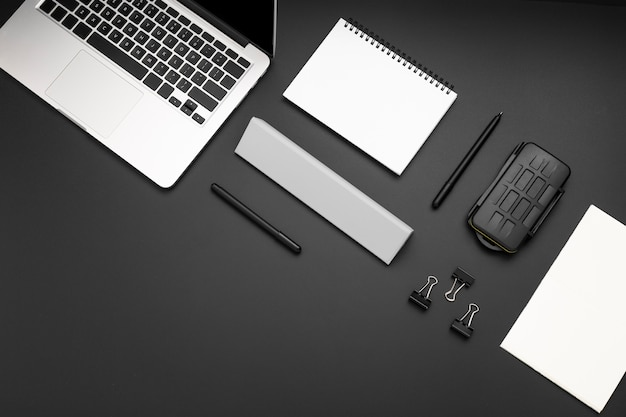Vista superior del espacio de trabajo con laptop y clips