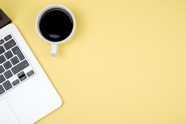 Vista superior del espacio de trabajo con laptop, taza de café y espacio de copia