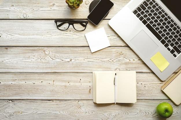 Vista superior del espacio de trabajo de la mesa de oficina. escritorio de madera con laptop, dispositivos y planta.