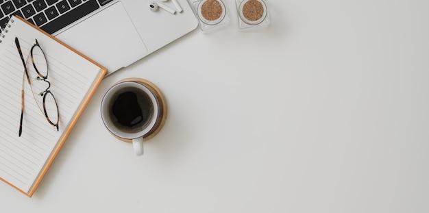 Vista superior del espacio de trabajo mínimo con computadora portátil, una taza de café y útiles de oficina