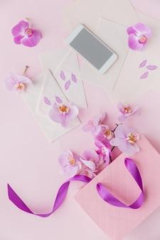 Vista superior del espacio de trabajo de la oficina en casa rosa con teléfono, cartas, flores y bolsa de regalo. plano de redes sociales con flores, papeles y teléfono inteligente. lugar de trabajo floral rosa femenino