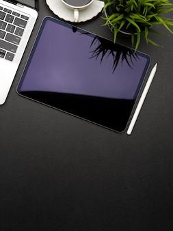 Vista superior del espacio de trabajo oscuro y creativo plano laico con tableta digital, computadora portátil, maceta y espacio de copia