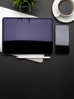 Vista superior del espacio de trabajo oscuro y creativo plano laico con tableta digital, teléfono inteligente, computadora portátil, taza de café y espacio para copiar