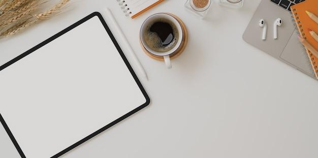 Vista superior del espacio de trabajo de otoño con tableta de pantalla en blanco, taza de café y útiles de oficina