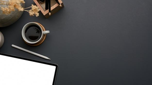 Vista superior del espacio de trabajo con tableta, café, decoraciones y espacio para copiar en la mesa