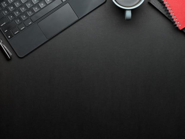 Vista superior del espacio de trabajo con teclado portátil, taza de café, cuadernos y espacio para copiar en la sala de la oficina en casa