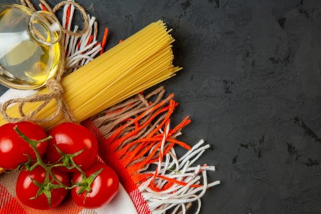 Vista superior de espagueti crudo y atado con una botella de hilo con aceite de oliva y tomates frescos en negro