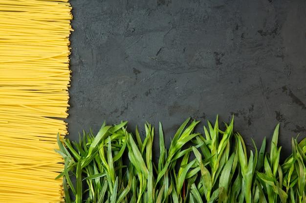 Vista superior de espagueti crudo y estragón fresco con espacio de copia en el medio sobre hormigón negro