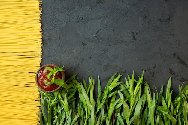 Vista superior de espagueti crudo salsa de tomate fresca y estragón con espacio de copia en el medio sobre hormigón negro