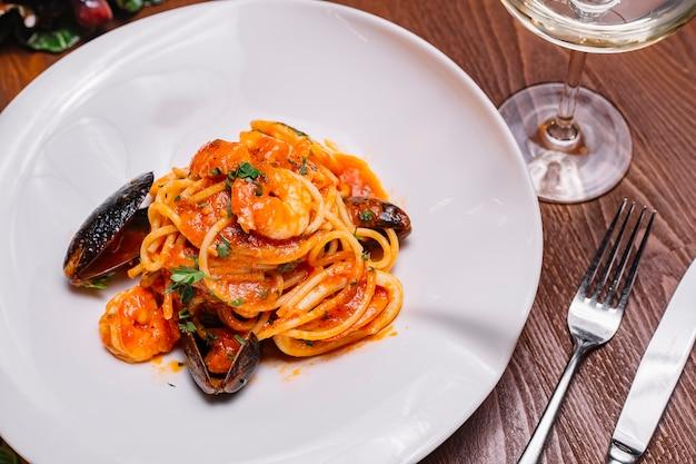 Vista superior de espagueti de mariscos con mejillones, camarones, salsa de tomate y perejil