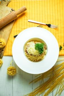 Vista superior de espaguetis a la boloñesa con parmesano en un tazón blanco sobre amarillo