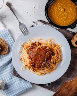 Vista superior de espaguetis a la boloñesa en plato blanco