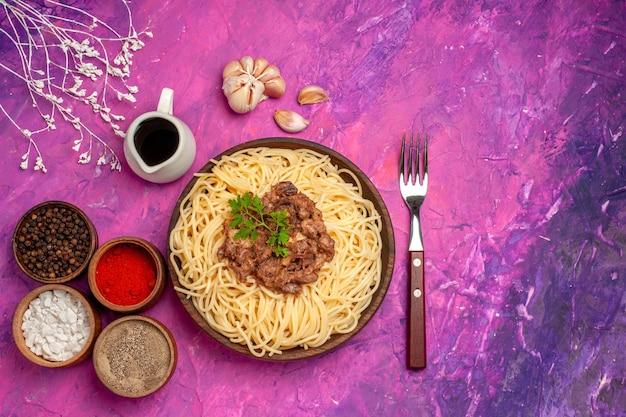 Vista superior de espaguetis cocidos con carne molida en el plato de condimento de mesa rosa pasta de masa