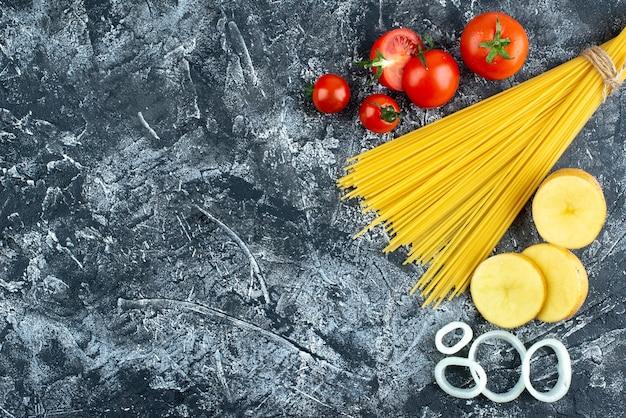 Vista superior de espaguetis con patatas, aros de cebolla y tomates