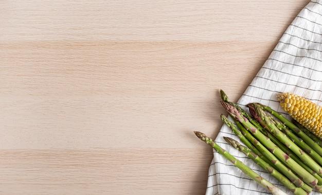 Vista superior de espárragos y maíz en una toalla de cocina con espacio de copia