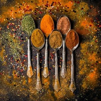 Vista superior de especias con pimienta y canela y cúrcuma en cuchara