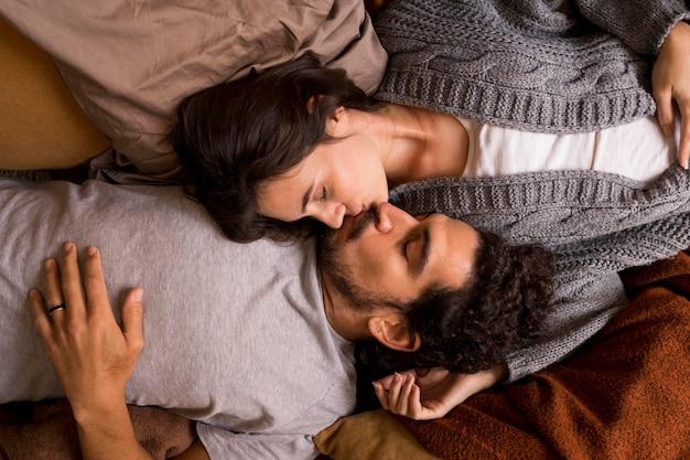 Vista superior de la esposa y el esposo besándose mientras está acostado en la cama