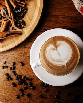Vista superior de espresso caliente junto con semillas de café y canela en el piso de madera marrón