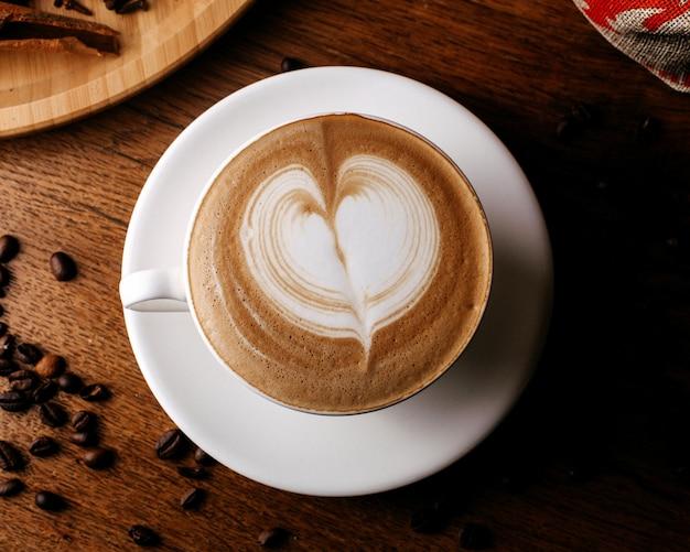 Vista superior espresso caliente sabroso dentro de un pequeño plato blanco en la superficie marrón