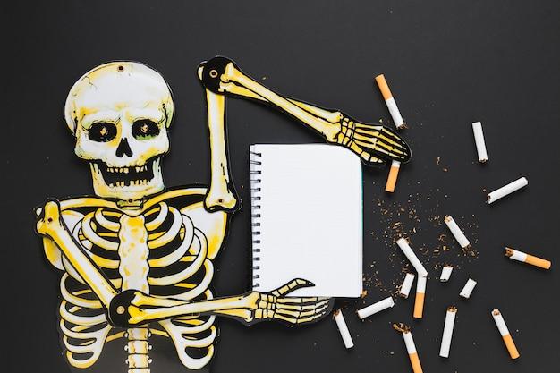 Vista superior esqueleto con cigarros y cuaderno