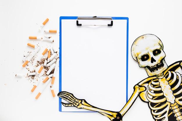 Vista superior esqueleto con cigarros
