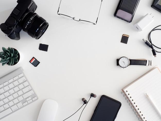 Vista superior de la estación de trabajo del fotógrafo, concepto de espacio de trabajo con cámara digital, tarjeta de memoria, teclado y teléfono inteligente sobre fondo blanco de mesa