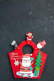 Vista superior del estado de ánimo navideño con accesorios de decoración y caja de regalo de año nuevo en una superficie oscura