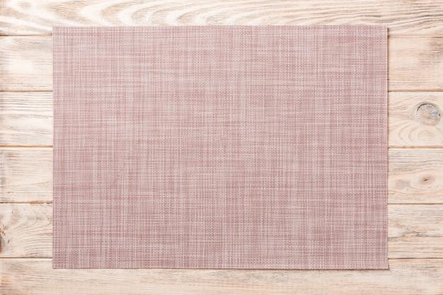 Vista superior de estera textil marrón para la cena sobre fondo de madera con espacio de copia