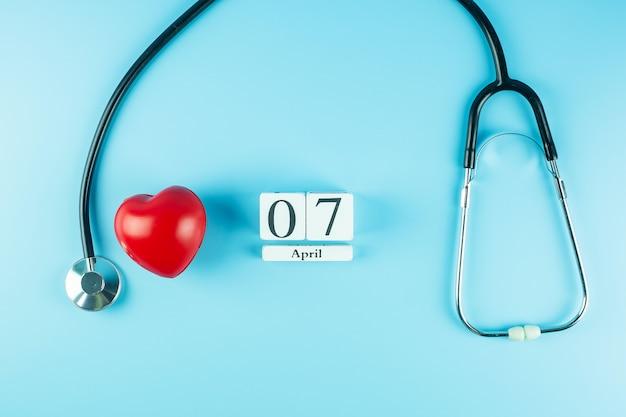 Vista superior estetoscopio, forma de corazón rojo y calendario del 7 de abril. día mundial de la salud