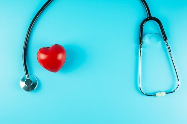 Vista superior estetoscopio con forma de corazón rojo sobre fondo azul con espacio de copia de texto. concepto de salud, seguro de vida, día de la salud, día mundial del corazón y día del médico feliz