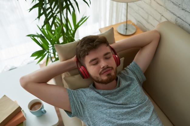 Vista superior del estudiante relajante en auriculares disfrutando de su lista de reproducción lounge