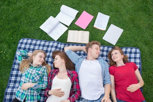 Vista superior de estudiantes tumbados en mantel de picnic
