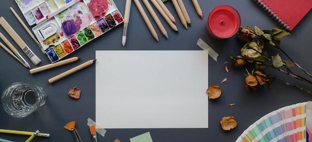 Vista superior del estudio del artista con bocetos, herramientas de pintura, acuarelas y útiles de oficina.