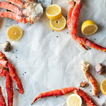 Vista superior de las falanges de cangrejo con limón y especias sobre papel arrugado.