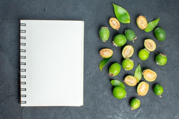 Vista superior feijoas frescas un cuaderno sobre superficie oscura