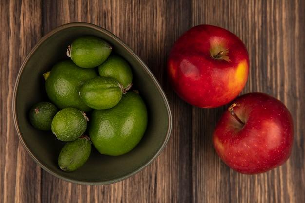 Vista superior de feijoas frescas con limas en un recipiente con manzanas rojas aisladas sobre una superficie de madera