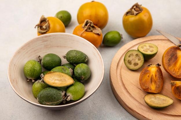 Vista superior de feijoas frescas en un recipiente con rodajas de caquis y feijoas sobre una tabla de cocina de madera sobre una superficie gris