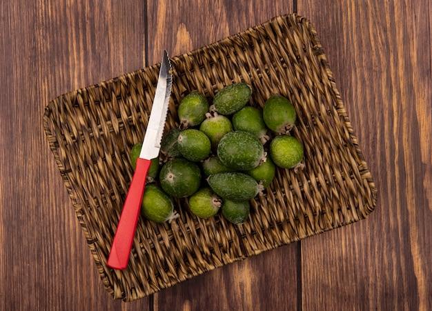 Vista superior de feijoas verdes frescas en una bandeja de mimbre con cuchillo sobre una superficie de madera