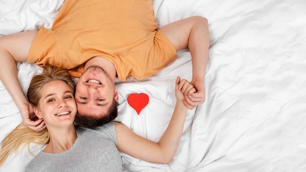 Vista superior feliz pareja cogidos de la mano en la cama
