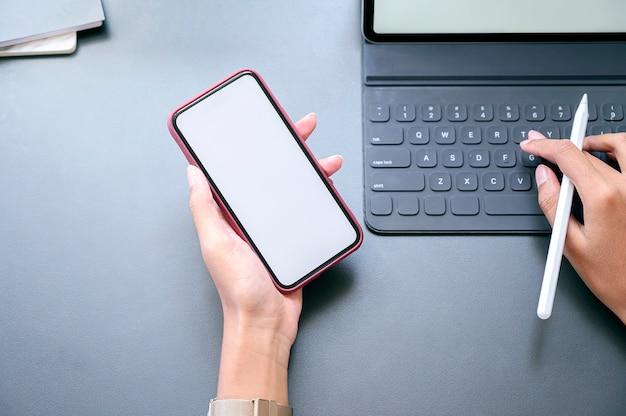Vista superior femenina mano smartphone con pantalla en blanco y trabajando con tableta.