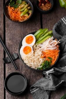 Vista superior de fideos asiáticos tradicionales con huevos y palillos