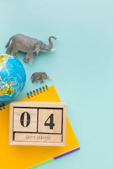 Vista superior de figuritas de elefantes con el planeta tierra y cuaderno para el día de los animales