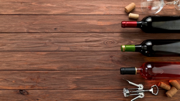 Vista superior fila de botellas de vino sobre fondo de madera