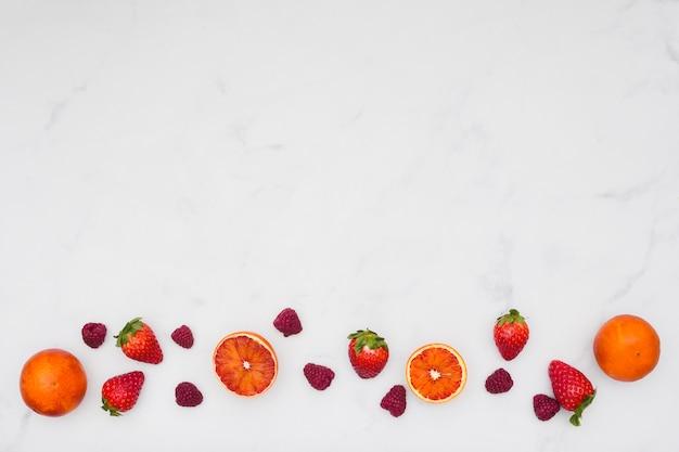 Vista superior fila de naranjas y fresas