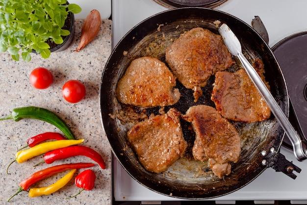 Vista superior del filete de cerdo asado en la sartén rústica