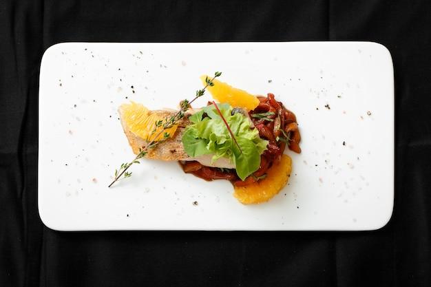 Vista superior de filete de pescado blanco con guiso de verduras